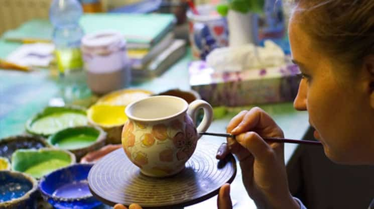 Woman working In her pottery studio. Ceramic workshop. Paint on