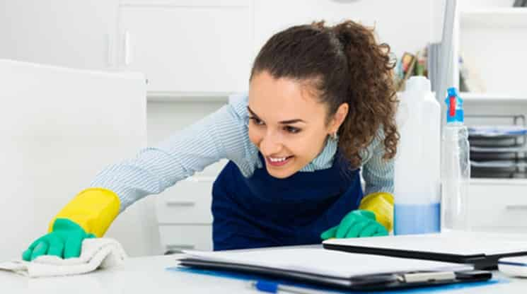 Glad woman in uniform cleaning in office